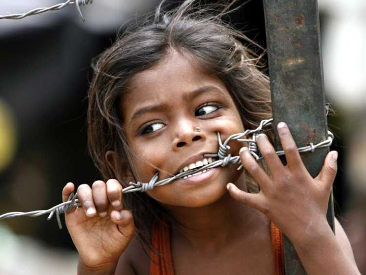 A child bites a barbed wire after a slum fire gutted dozens of huts in New Delhi
