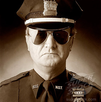 Studio portrait of stern-looking policeman in sunglasses